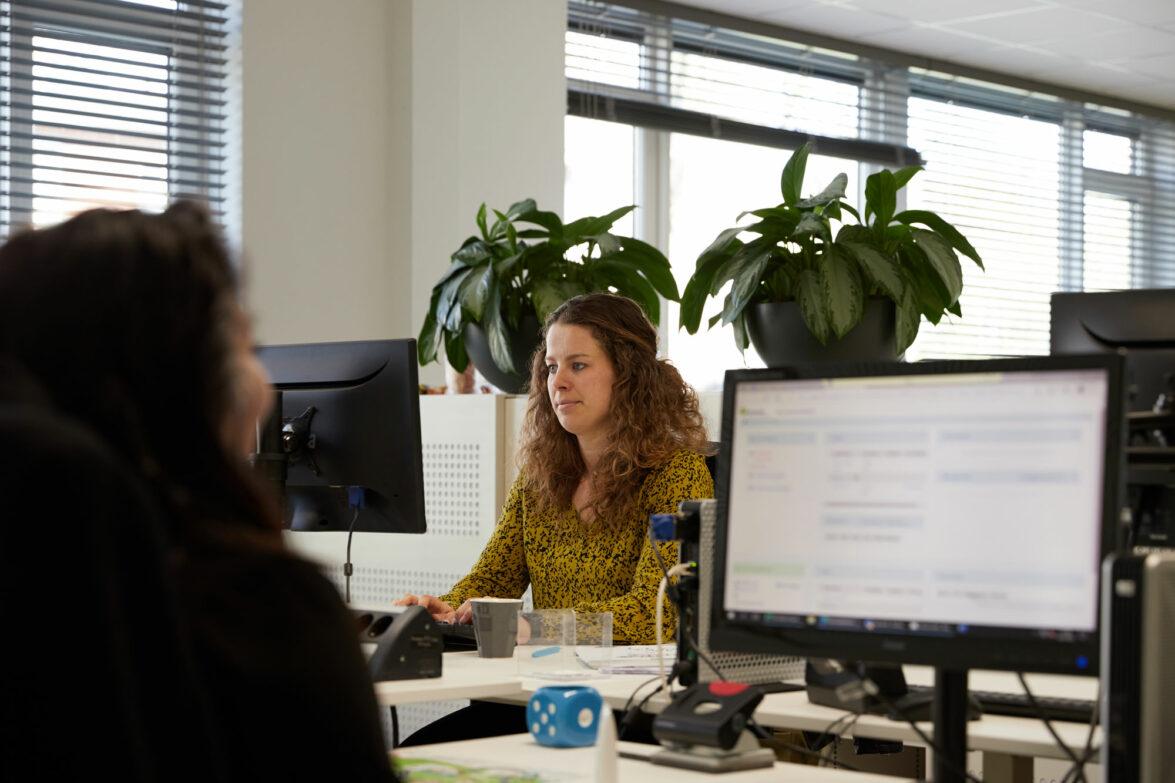 Medewerkster van Traverse zit achter de computer op kantoor.