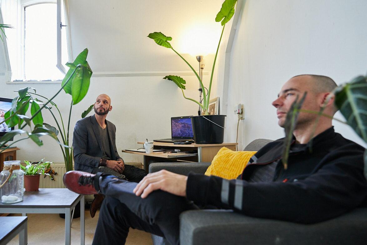Twee mannen (cliënt en persoonlijk coach) zitten samen in de studio van de cliënt en kijken naar een persoon buiten beeld.