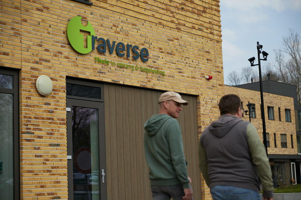Twee mannen lopen bij de hoofdingang van Traverse